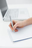 Close up of a hand writing notes by laptop Stock Photography