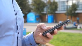 Close up hand of young businessman holding and touching smartphone. Unrecognizable man standing on urban street and stock footage