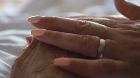 Close up hand of young woman gentle stroking her sick mother giving support. Daughter comforting wrinkled arm elderly