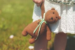 Close-up of a handbag with a bouquet and a knitted bear peeking out of it in the hands of a girl on a meadow with royalty free stock images