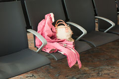 Close-up of handbag and coat on the chair at the airport. Travel, vacation, business concept. Stock Photo