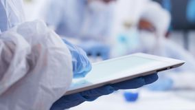 Close up handheld footage of chemist typing on tablet in a research laboratory. Team of scientist working in the background. Scientist in coverall equipment stock footage