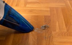 Vacuum cleaner hoovering dirt from floor Stock Photography