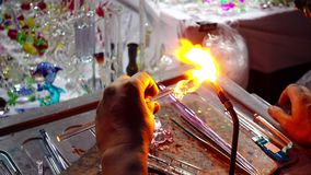 Close up handicrafts glass maker making a glass subject. By melting glass with a flaming torch from blowtorch on new glass art piece stock footage