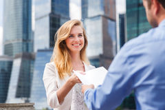 Close-up of handing over documents during business briefing. In city street Royalty Free Stock Photography