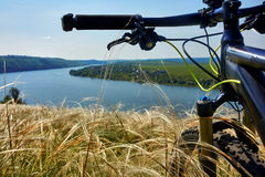 Close-up of the handlaber of mountain bicycle against beautiful landscape in summer season. royalty free stock photography