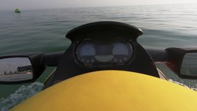 Close up of the handle bars and mirror of jet ski. Detail of yellow jet ski driving on the water. Holiday water sports stock video