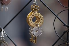 Close up of handmade golden and silver earrings, with clock dial, key and spur.  Royalty Free Stock Photo