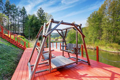 Close up of handmade two swinging benches on red wooden deck. Stock Images