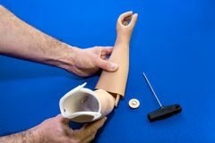 Close up on hands adjusting prosthetic arm Royalty Free Stock Image
