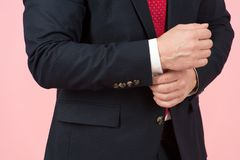 Close-up of hands adjusting white sleeve in blue suit. Close-up of hands adjusting white sleeve in dark blue suit. Man accessories - buttons and ties Stock Photo