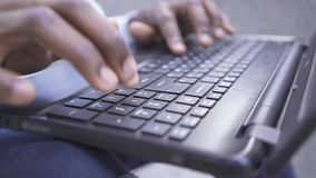 Close-up hands of African American man typing fast on the keyboard of his laptop. Confident male businessman or manager stock video