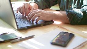 Close up on hands of anonymous man working on laptop. Phone onthe table stock footage