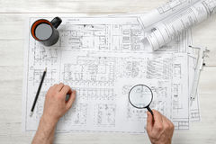 Close-up hands of architect while working process with magnifying glass Royalty Free Stock Photos
