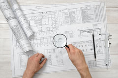 Close-up hands of architect while working process with magnifying glass. Royalty Free Stock Photos