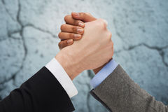 Close up of hands arm wrestling over concrete wall Stock Photo
