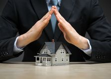 Close up of hands as roof over little house Royalty Free Stock Photo