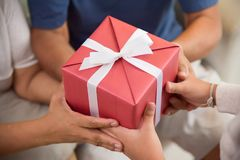 Asian boy giving a red gift box to Grandfather and Grandmother. Close up on hands. Asian Boy giving a red gift box to his Grandfather and Grandmother for stock photo