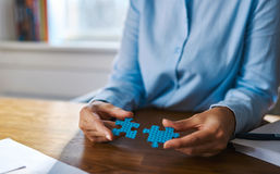 Close up of hands assembling two puzzle pieces Royalty Free Stock Photo