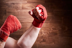 Close-up of hands with bandage of boxer ready for a fight against wooden wall. Royalty Free Stock Images