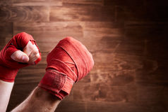 Close-up of hands with bandage of boxer ready for a fight against wooden wall. Royalty Free Stock Photo