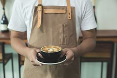 Close up hands of barista man holding cup of hot latte coffee in. The cafe Stock Photo