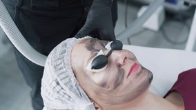 Close-up hands beautician makes carbon peeling procedure on young woman face in clinic, slow motion. Laser flash cleans skin of patient face stock video footage
