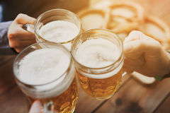 Close up of hands with beer mugs at bar or pub. People, leisure and drinks concept - close up of male hands clinking beer mugs at bar or pub Royalty Free Stock Photos