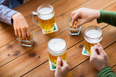 Close up of hands with beer mugs at bar or pub Royalty Free Stock Images