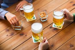 Close up of hands with beer mugs at bar or pub Stock Images