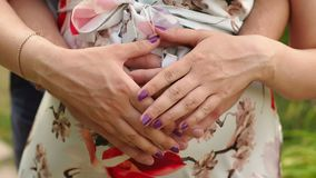 Close-up of hands on belly of pregnant woman. stock video