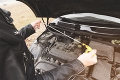 Girl opening the hood of her car checks the engine oil level. Close-up of the hands The blond girl opens the hood of her car and checks the engine oil level. The Royalty Free Stock Photos