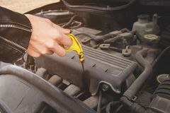 Girl opening the hood of her car checks the engine oil level. Close-up of the hands The blond girl opens the hood of her car and checks the engine oil level. The Royalty Free Stock Photography