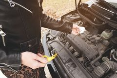 Girl opening the hood of her car checks the engine oil level. Close-up of the hands The blond girl opens the hood of her car and checks the engine oil level. The Stock Photography