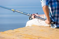 Close-up of hands of a boy with a fishing rod. That is fishing on the pier royalty free stock photo