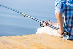 Close-up of hands of a boy with a fishing rod Royalty Free Stock Images