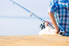 Close-up of hands of a boy with a fishing rod. That is fishing on the pier royalty free stock photos