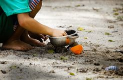Kid play sand in the park. Close up hands of a boy are grinding sand under light and shade royalty free stock photo
