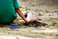 Kid play sand in the park. Close up hands of a boy are grinding sand under light and shade royalty free stock photos