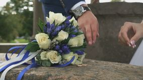 Close-up of hands of bride and groom outdoors. Close-up of hands of bride and groom taking wedding rings from the marble stone during wedding registration stock footage