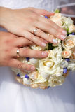 Close up  hands of bride and groom with wedding bouquet Stock Photography
