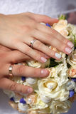 Close up  hands of bride and groom with wedding bouquet Stock Image