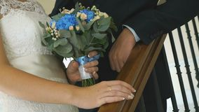 Close-up of hands of bride and groom outdoors. Close-up of hands of bride holding wedding bouquet of roses and hand of the groom on railings indoors stock video footage