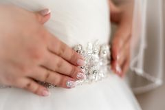 Close up hands of bride touch jewellery on dress stock photography