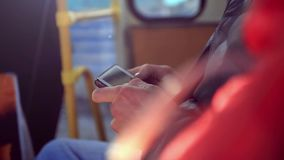 Close-up hands in bus man using his cell phone stock video footage