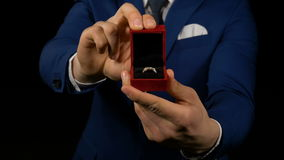 Close-up with hands of business man opening small a gift box with ring inside. Close up with hands of business man opening small gift box with ring inside stock video