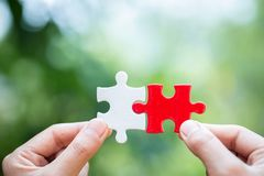 Close up of hands business women connecting jigsaw puzzle, Teamwork workplace success and strategy concept stock photo