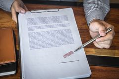 Close up hands of businessman pointing to signing and stamp on paper document to approve business investment contract agreement stock photography
