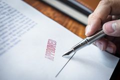 Close up hands of businessman signing and stamp on paper document to approve business investment contract agreement.  stock photo