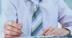 Close up of the hands of a businessman in a suit signing or writing a document on a sheet of white paper. stock image